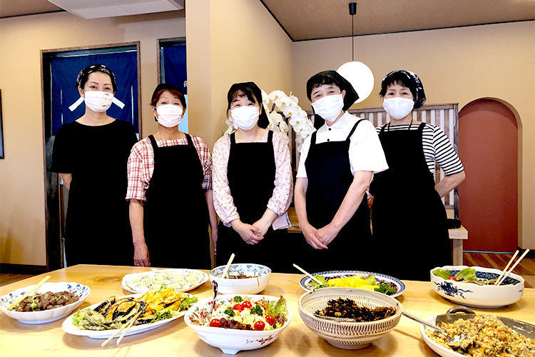 長浜食堂笑顔の女性職員と色とりどりのお惣菜の写真